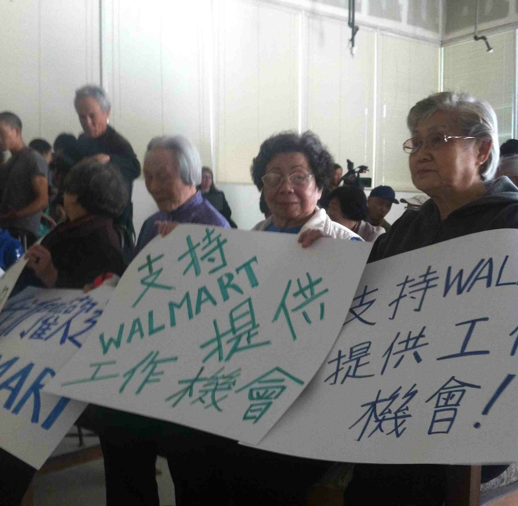Chinatown residents hold signs in support of Walmart.