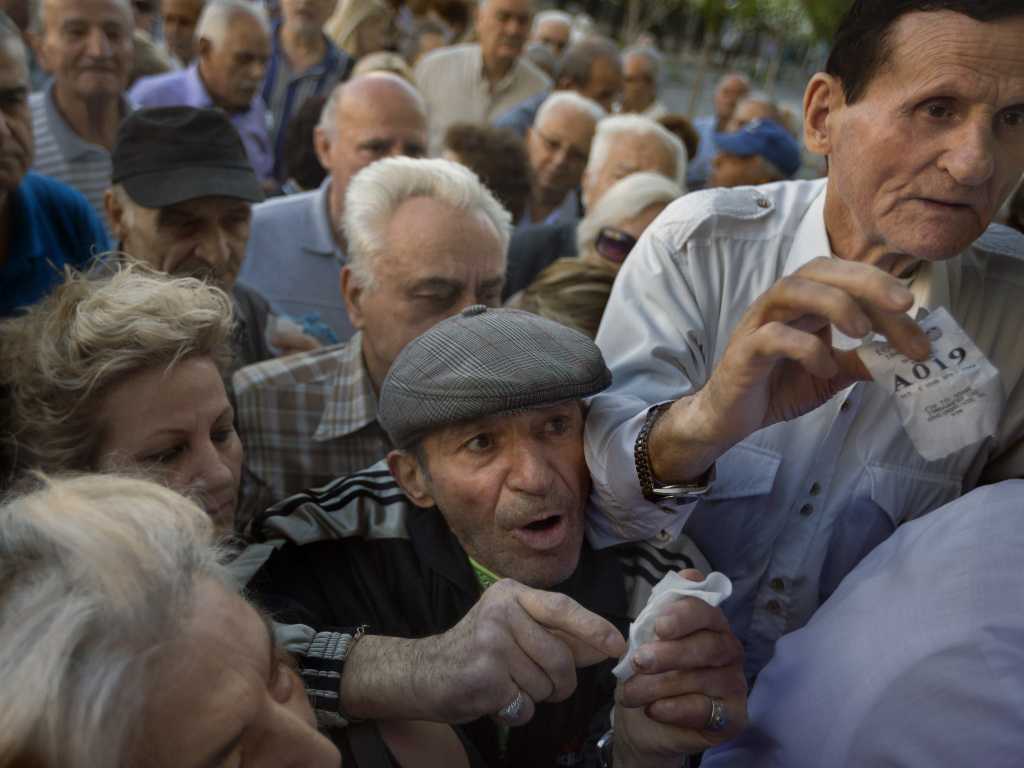 Pensioners holding their queue numbers try to enter a bank in Athens.