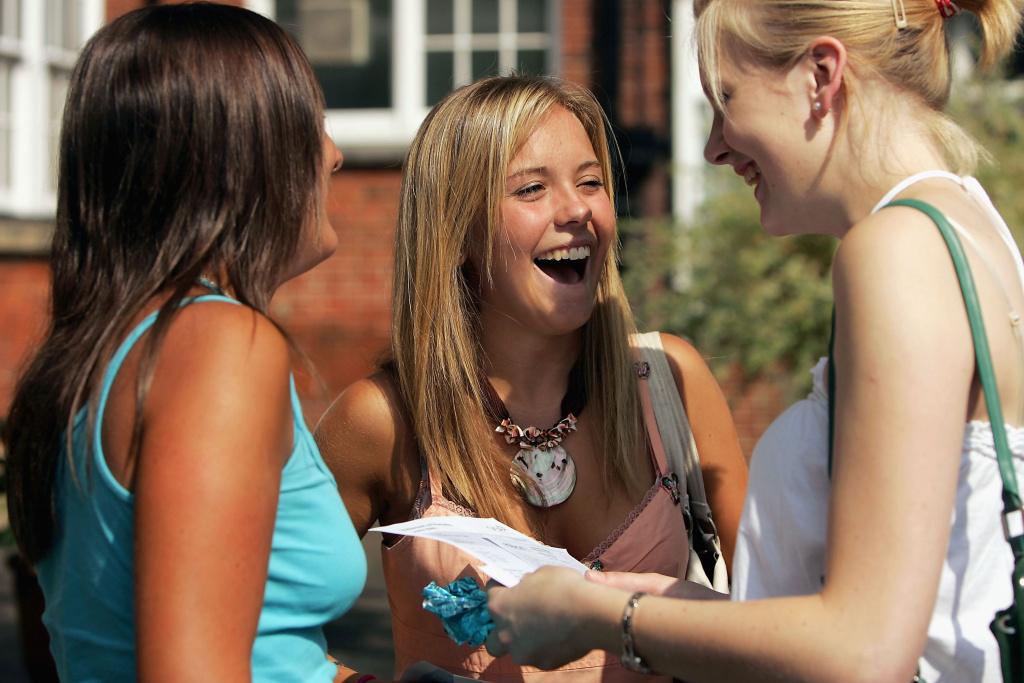 A group of students congratulate each other after reading their 'A' Level grades.