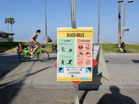 A sign displaying beach rules hangs along Venice Beach, where beachgoers returned this weekend following weeks of lockdown due to the coronavirus.