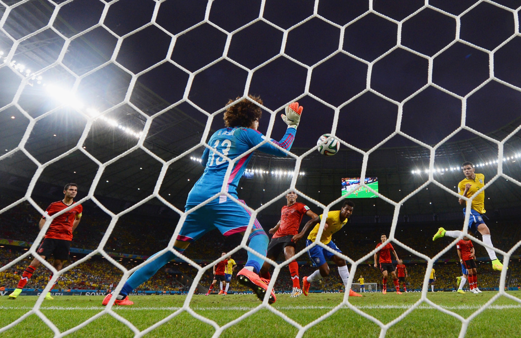 Guillermo Ochoa of Mexico makes a save after a header by Thiago Silva of Brazil (R) during the 2014 FIFA World Cup Brazil Group A match between Brazil and Mexico at Castelao on June 17, 2014 in Fortaleza, Brazil.