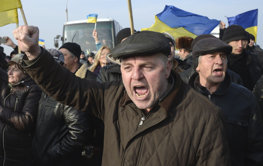 Ukrainians carrying their country's flags stage a protest at the Chongar check point blocking the entrance to Crimea on March 7, 2014.