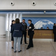 Travellers stand in front of an information desk at Pyongyang airport on April 17, 2017.
