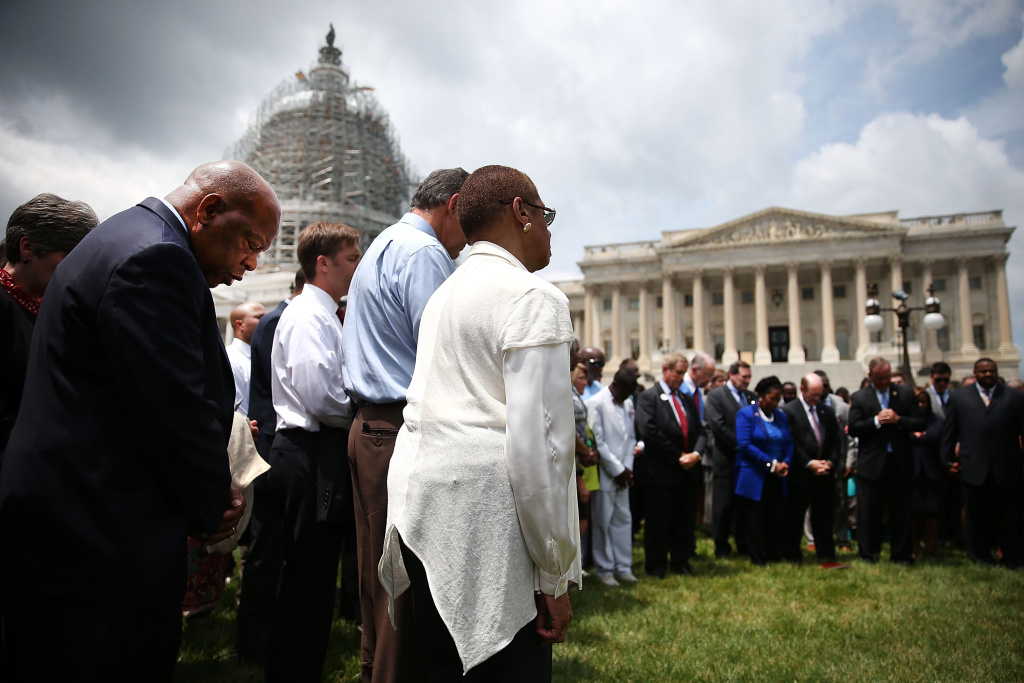 Rep. John Lewis (D-GA) (L) joins members of the US House of Representatives and members of the US Senate in a prayer circle in front of the US Capitol to honor those gunned down last night inside the historic Emanuel African Methodist Episcopal Church in Charleston South Carolina, June 18, 2015 in Washington, DC.