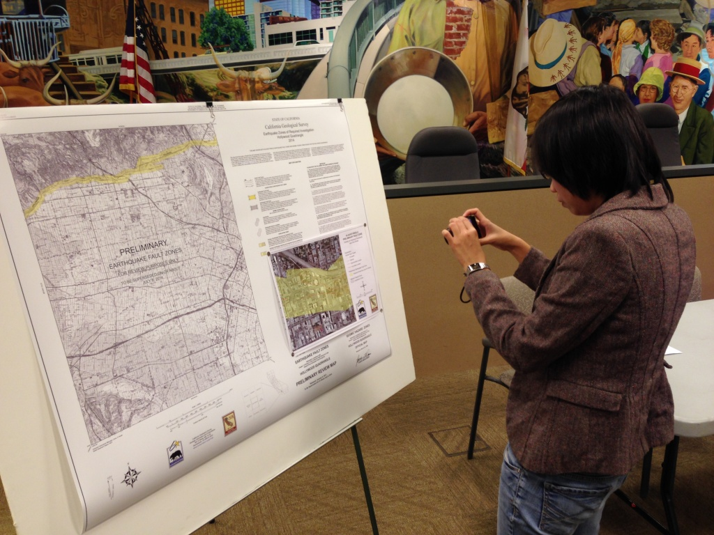 A woman takes a photo of the new Hollywood earthquake fault map released by the California Geological Survey Wednesday.