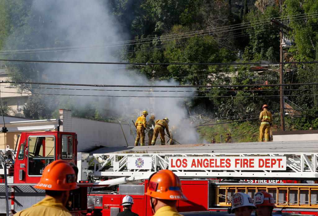 Los Angeles firefighters knock down hot spots on the roof of a music studio in Los Angeles Saturday, April. 14, 2018. Officials says two people were killed and at least three others were hurt when flames ripped through the studio.