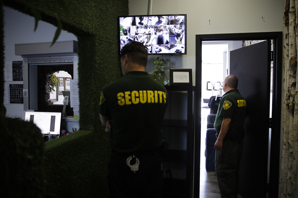 In this June 27, 2017, photo, two security guard workers at the Higher Path medical marijuana dispensary owned by Jerred Kiloh in Los Angeles. Kiloh's dispensary on a busy commercial strip is a target for robbers and it's been hit twice, once by burglars who broke in through the roof.