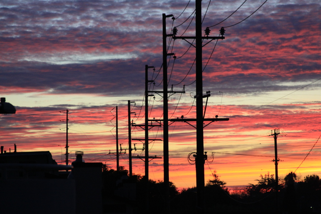 The sun sets behind a row of power lines.