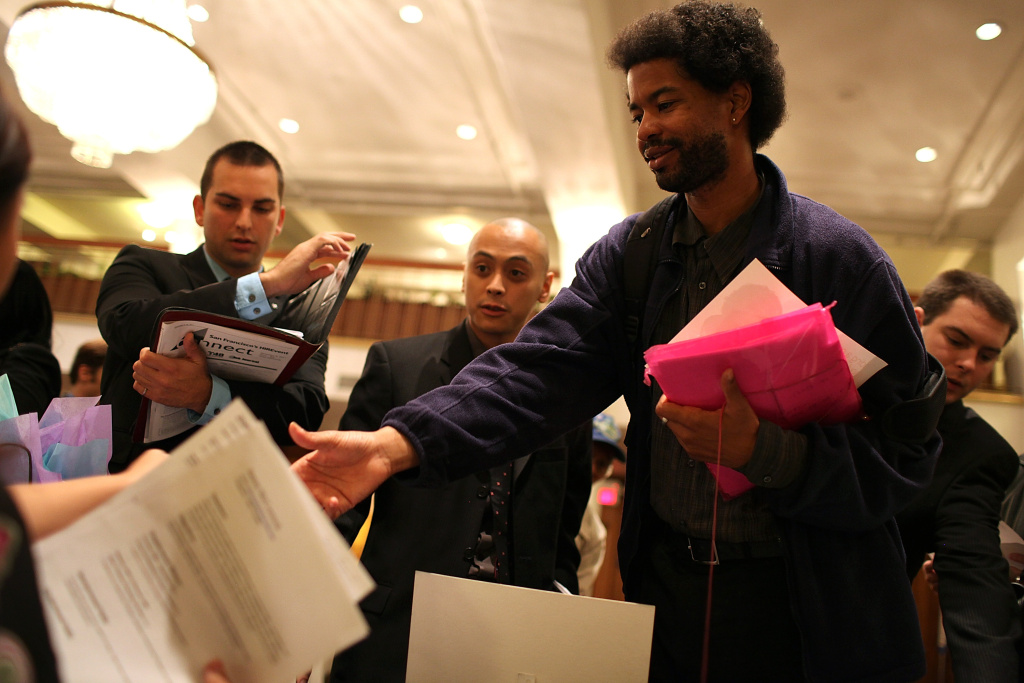 Job seekers hand out resumes to a recruiter during the San Francisco Hire Event job fair on November 9, 2011 in San Francisco, California.