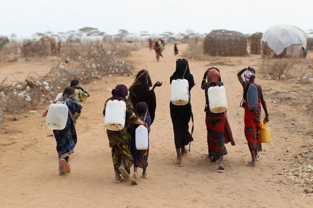 Somalian refugees return from collecting water at the edge of the Dagahaley refugee camp which makes up part of the giant Dadaab refugee settlement on July 22, 2011 in Dadaab, Kenya.