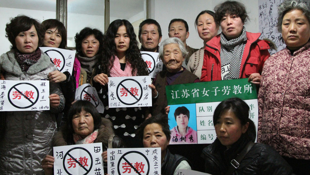 Some former prisoners of re-education through labor camps and their supporters hold signs in Beijing declaring,