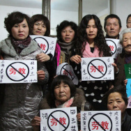 "Some former prisoners of re-education through labor camps and their supporters hold signs in Beijing declaring, ""No Re-education Through Labor."" Popular opposition to the camps has grown as China's state-run media has highlighted particularly egregious ca"