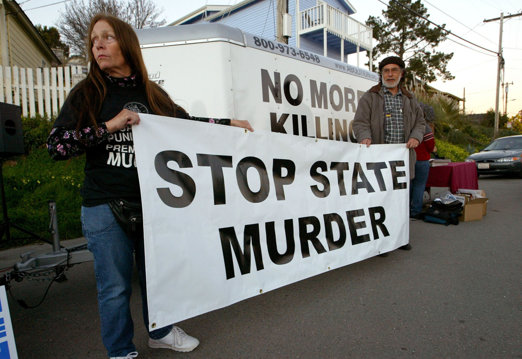 Melanie Bostic (left) of Lancaster, California and Michael Wharton of San Leandro, California hold a sign outside of the California State Prison at San Quentin on February 9, 2004. A decision by an 11-judge panel of the 9th U.S. Circuit Court of Appeals on Monday barred the execution of convicted killer Kevin Cooper, saying evidence in his case should get a fresh look after 18 years of appeals.