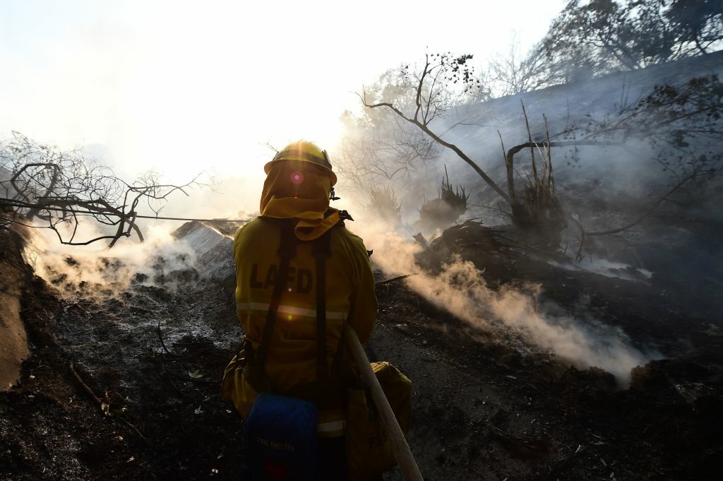 A firefighter controls flames burning in a home at the Skirball Fire in the upscale Bel- Air section of west Los Angeles, California, December 6, 2017. California motorists commuted past a blazing inferno Wednesday as wind-whipped wildfires raged across the Los Angeles region, with flames  triggering the closure of a major freeway and mandatory evacuations in an area dotted with mansions. / AFP PHOTO / Robyn Beck        (Photo credit should read ROBYN BECK/AFP/Getty Images)