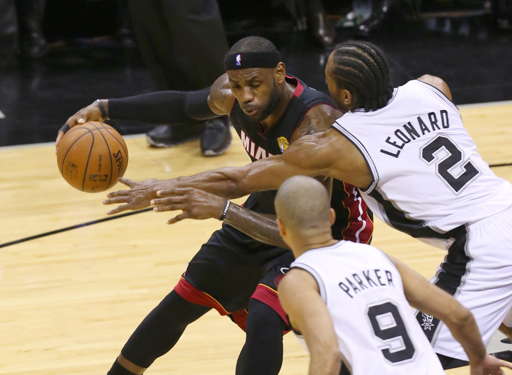 LeBron James #6 of the Miami Heat drives into Kawhi Leonard #2 of the San Antonio Spurs in Game Five of the 2014 NBA Finals at the AT&T Center on June 15, 2014 in San Antonio, Texas.