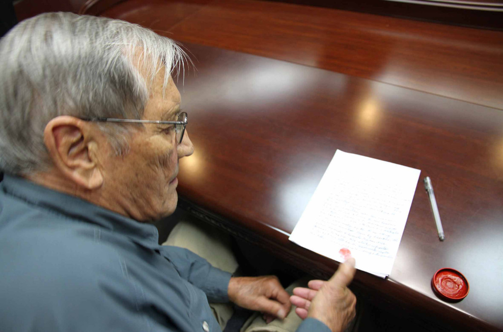 This photo taken on November 9, 2013 and released on Novermber 30, 2013 by North Korea's official Korean Central News Agency (KCNA) shows U.S. citizen Merrill Newman inking his thumbprint onto a written apology for his alleged crimes both as a tourist and during his participation in the Korean War.