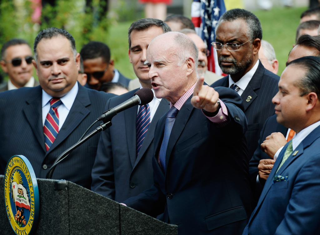 California Governor Jerry Brown speaks before signing bill AB60 on the steps of Los Angeles City Hall  October 3, 2013 in Los Angeles, California. California Assembly Bill 60 also known as the Safe and Responsible Driver Act allows illegal immigrants to receive a permit to legally drive in California.