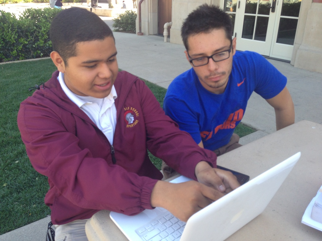 Juan Vasquez (right) of the non-profit URBAN TxT helps a South L.A. high school student learn skills to create apps and develop tech projects.