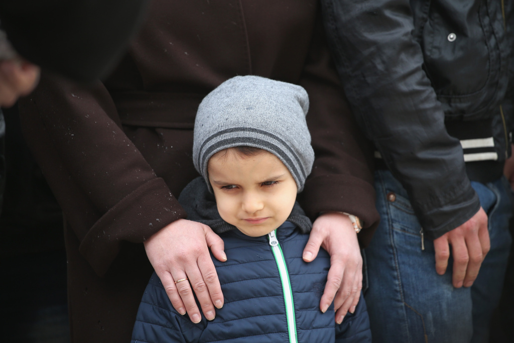 A young boy waits for a priest to bless him in Donetsk, Ukraine.