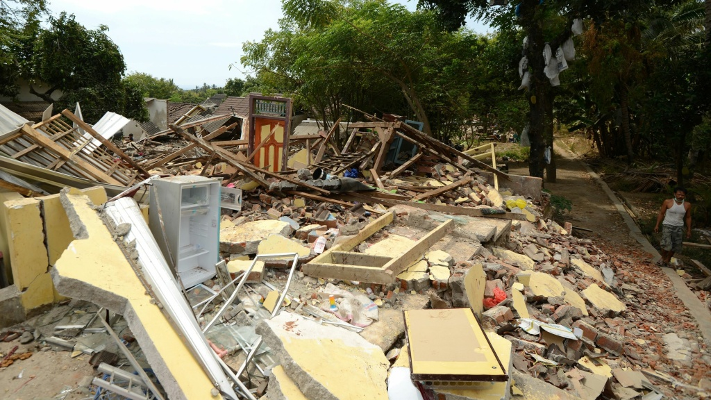 A man walks past collapsed houses in Kayangan, on the Indonesian island of Lombok, on Thursday. A devastating earthquake on Sunday killed hundreds, and a strong aftershock on Thursday caused panic among evacuees.
