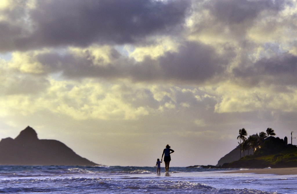 Anne Kllingshirn, of Kailua, Hawaii walks with her daughter Emma, 1, as storm clouds float overhead during the sunrise hours on Kailua Beach, in Kailua, Hawaii, Thursday morning Aug. 7, 2014. The National Weather Service downgraded Hurricane Iselle to a tropical storm about 50 miles before it was expected to make landfall early Friday in the southern part of Hawaii's Big Island. By 2 a.m. Hawaii Standard Time on Friday, the storm was swirling about 10 miles from the Kau coastline.