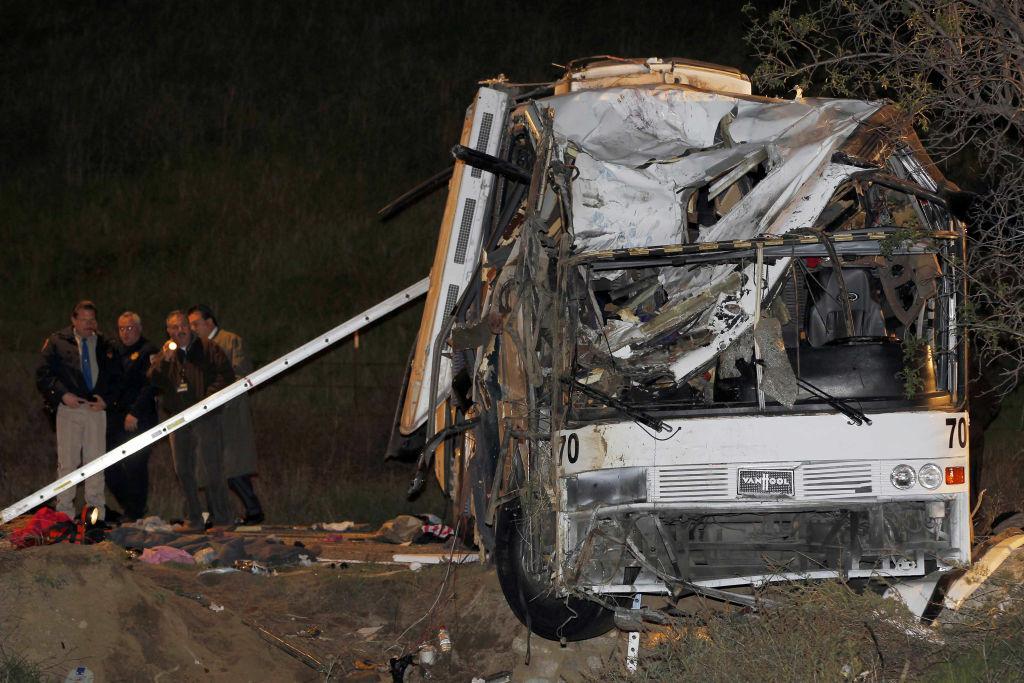 Investigators continue working the scene of a fatal tour bus crash near Yucaipa, Calif., Sunday, Feb. 3, 2013. (AP Photo/Nick Ut)