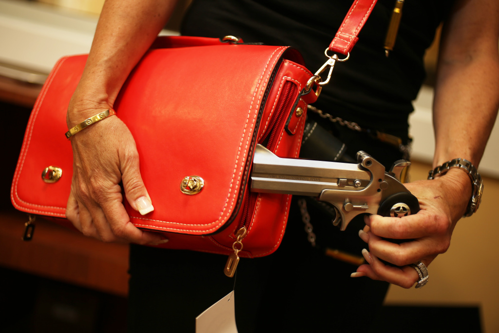 Susan Kushlin poses with a concealed-carry handbag that her company, Gun Girls, Inc., created for women that enjoy guns on October 21, 2013 in Boca Raton, Florida.