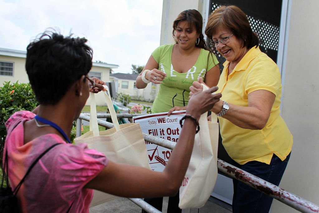 U.S. Census worker, Monique Stence, (L) gives census bags to Sandra Gutierrez (C) and Maria Martinez as they blanket a neighborhood during the
