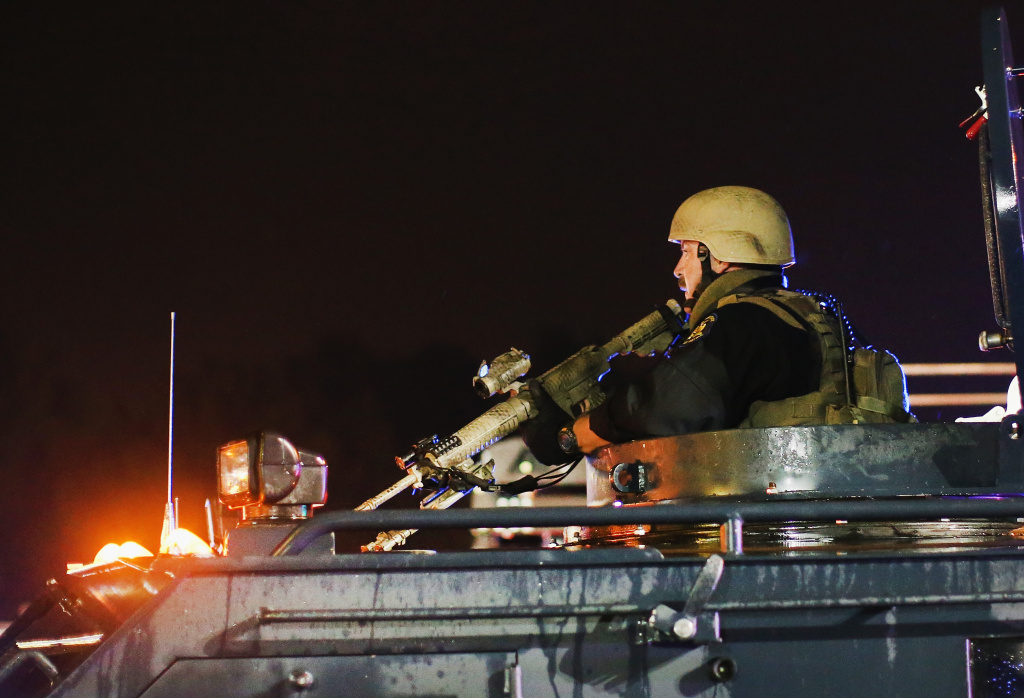 Police confront demonstrators during a protest over the shooting death of Michael Williams on Aug. 15, 2014 in Ferguson, Missouri. Police shot pepper spray,  smoke, gas and flash grenades at protesters before retreating. Several businesses were looted as the county police sat nearby with armored personnel carriers (APC). Violent outbreaks have taken place in Ferguson since the shooting death of Brown by a Ferguson police officer on Aug. 9.