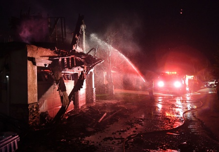 Firefighters hose down a burning house during the Tick Fire in Agua Dulce near Santa Clarita, California on October 25, 2019.