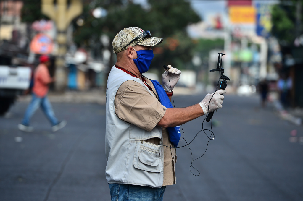 A journalist wears a face mask and gloves against the spread of the new coronavirus as he makes a live transmission near a street market in Tegucigalpa, on March 22, 2020.