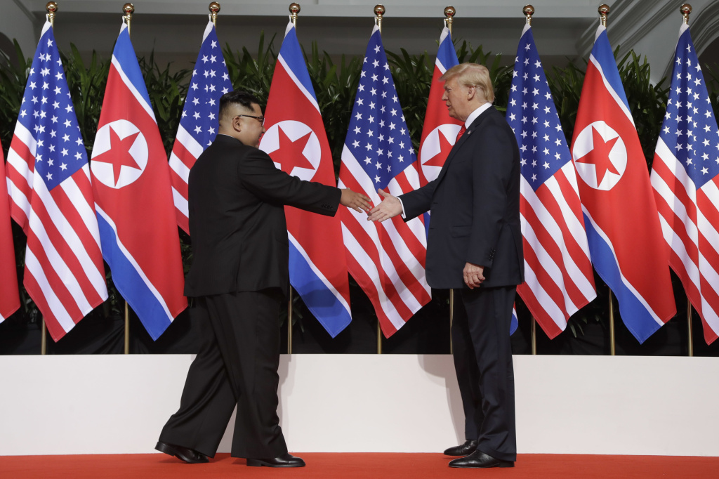 North Korean leader Kim Jong Un reaches to shake President Trump's hand at the Capella resort on Sentosa Island in Singapore on Tuesday.