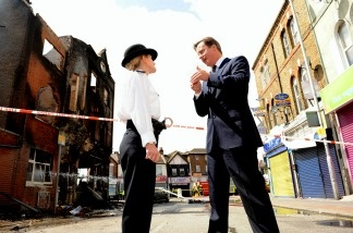 British Prime Minister David Cameron (R) talks to Acting Borough Commander Police Superintendent Jo Oakley in Croydon, south of London.