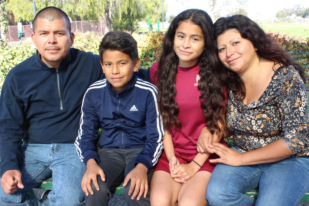 Crista Ramos sits on a park bench with dad Edgar Ramos, brother Diego and mom Cristina Morales in Richmond, Calif. on Nov. 4, 2018.