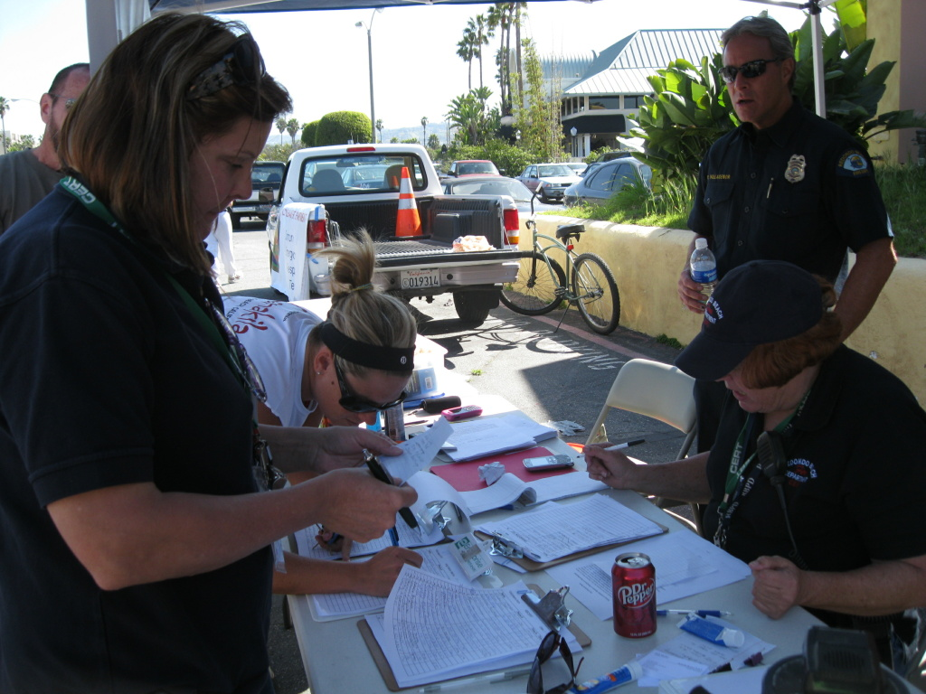 A volunteer signs up at the Redondo Beach Community Emergency Response Team table to help clean up dead fish in King Harbor in Redondo Beach on March 9, 2011.