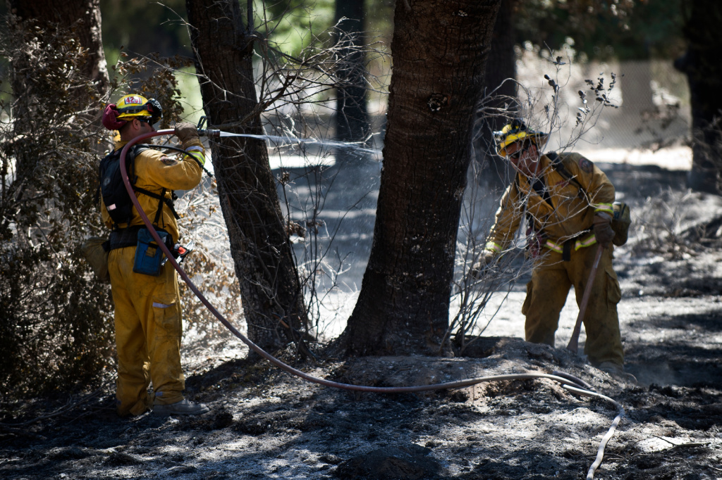 A CalFire crew puts out hot spots off of Highway 243 as the Silver Fire continues to burn in the San Jacinto Mountains near Banning, Calif. on Friday, Aug. 9.