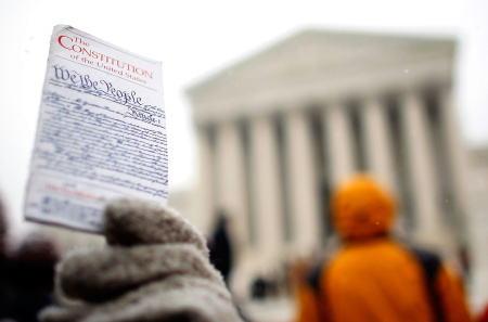 A protester holds up a copy of the U.S. Constitution while demonstrating in front of the U.S. Supreme Court December 5, 2007 in Washington, DC.