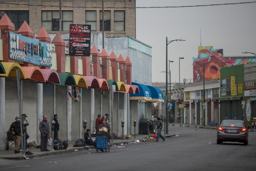 Homeless people mill around on a Skid Row sidewalk after packing up their tents for the day and before businesses open.
