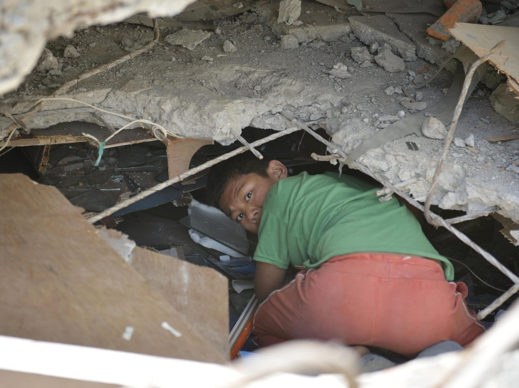 A boy crawls into the ruins of a collapsed building to look for usable things in Nepal capital Kathmandu on Sunday. Officials say they have found three survivors in the rubble a full week after a powerful earthquake.