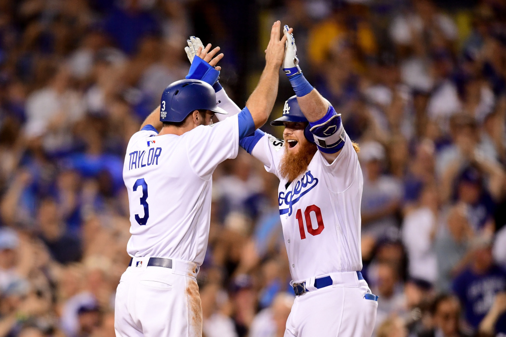 Justin Turner of the Los Angeles Dodgers celebrates with Chris Taylor after hitting a two-run home run during the sixth inning against the Houston Astros in game one of the 2017 World Series at Dodger Stadium on Oct. 24, 2017.