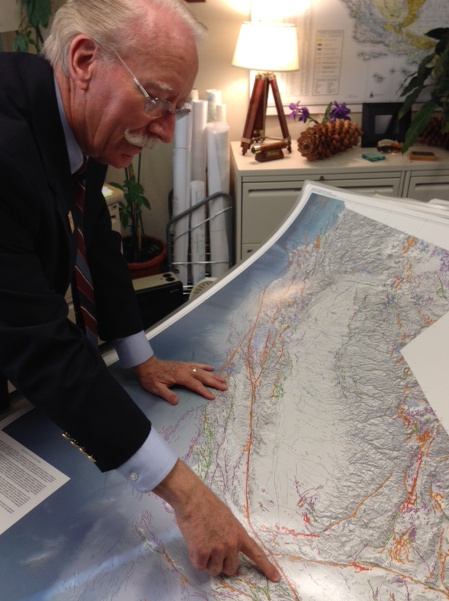 John Parrish shows off a state map with 15,000 faults on it. He says there are likely many more faults that have not yet been discovered.