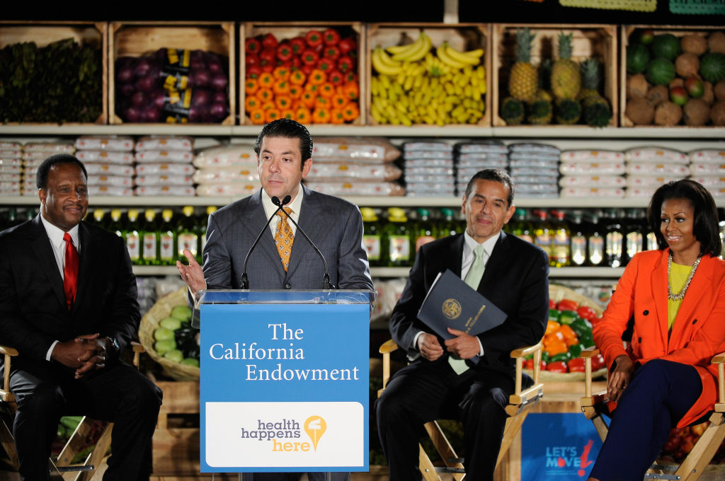 Oscar Gonzalez, co president of Northgare Gonzalez Markets, speaks speaks at the future site of Northgate Gonzalez Market as First lady Michelle Obama (R) Inglewood Mayor James Butts (L) Los Angeles City Mayor Antonio Villaraigosa (2ndR) look  look on February 1, 2012 in Inglewood, California. The $264 million public-private fund plans to bring healthy food stores to under-served communities and create or retain up to six thousand jobs. The fund has committed $20 million in financing to Northgate for the first three projects, which are in South Los Angeles, Inglewood and the City Heights portion of San Diego. The first lady will end her two-day visit with a television appearance to promote her fight against childhood obesity and a fundraiser for her husband U.S. President Barack Obama.
