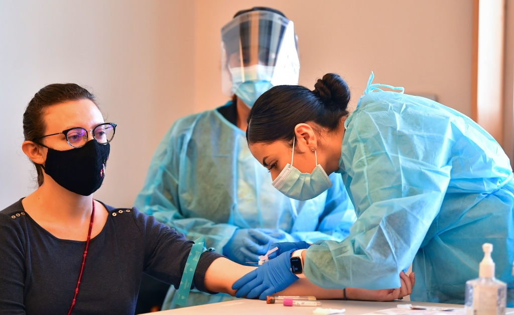 A phlebotomist draws blood at a free COVID-19 antibody testing event on Feb.17 in Pico Rivera, Calif.