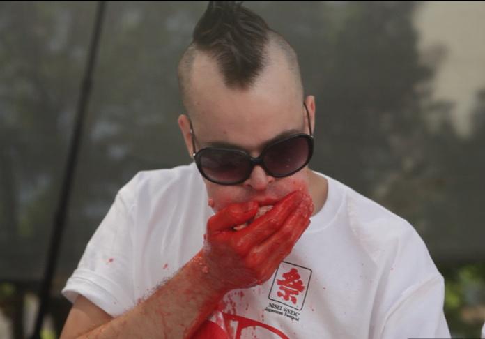 Competitive eater Takeru Kobayashi celebrates after breaking a hot dog eating record.