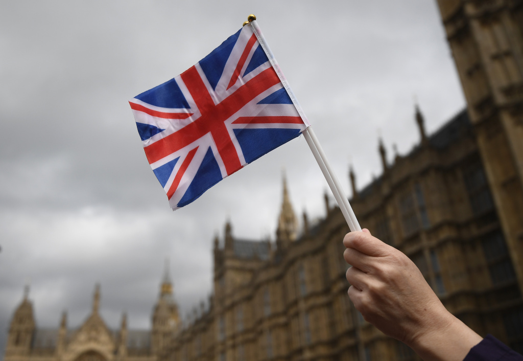 A Pro Brexit supporter holds a Union Jack flag during a small pro EU demonstration near Parliament on March 29, 2017 in London, England.