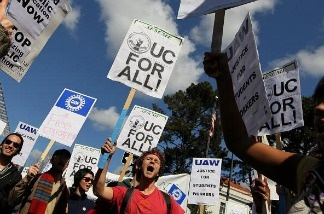 Students at UC Berkeley carry signs as they march through campus during a national day of action against funding cuts and tuition increases.