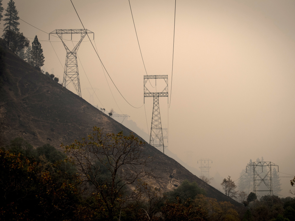 California utility PG&E Corp. said Monday that it plans to file for bankruptcy over what it estimates could be $30 billion in potential liability costs from recent wildfires. Here, transmission towers in a valley near Paradise, Calif., as the Camp Fire burns in November 2017.