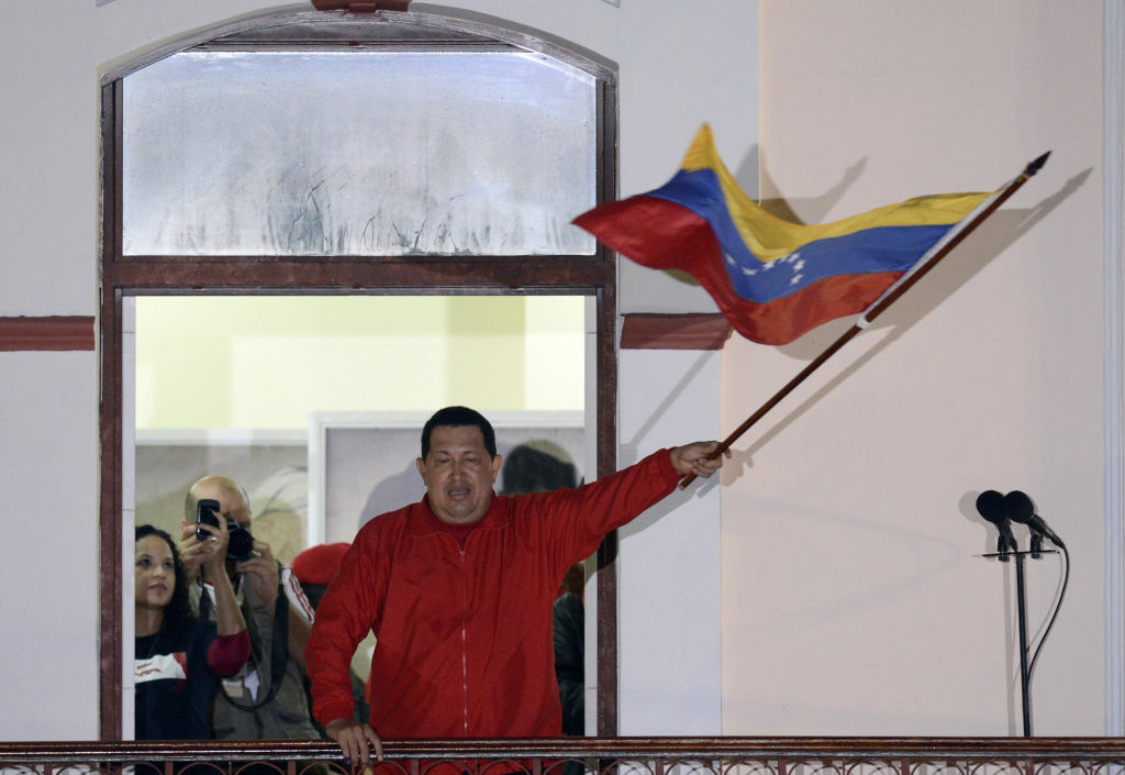 Venezuelan President Hugo Chavez waves a Venezuelan flag while speaking to supporters after receiving news of his reelection in Caracas on October 7, 2012. According to the National Electoral Council, Chavez was reelected with 54.42% of the votes, beating opposition candidate Henrique Capriles, who obtained 44.97%.