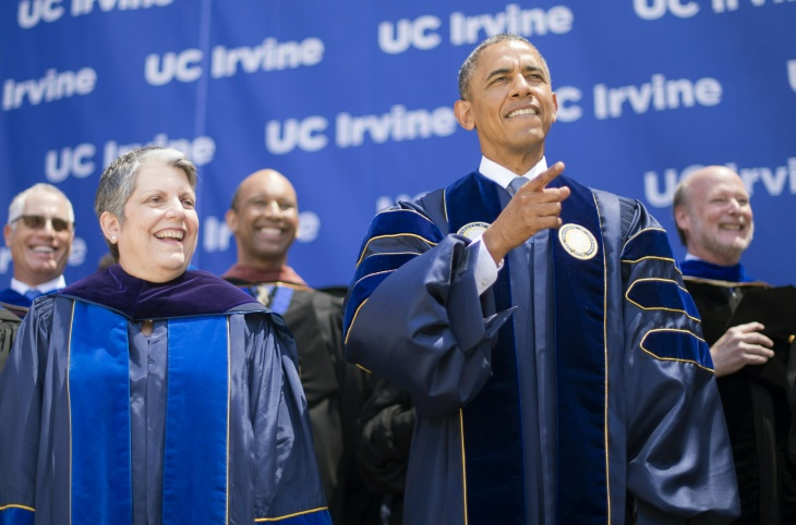 President Barack Obama (L) makes a ZOT sign, the symbol for the University of California Irvine Anteaters, as he arrives to deliver the commencement address June 14, 2014.