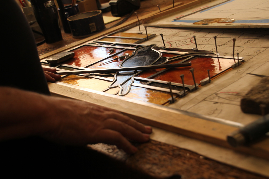 Craftsman Robert Youngman uses the same tools that have been used for centuries to assemble a stained glass window for a church in Covina.